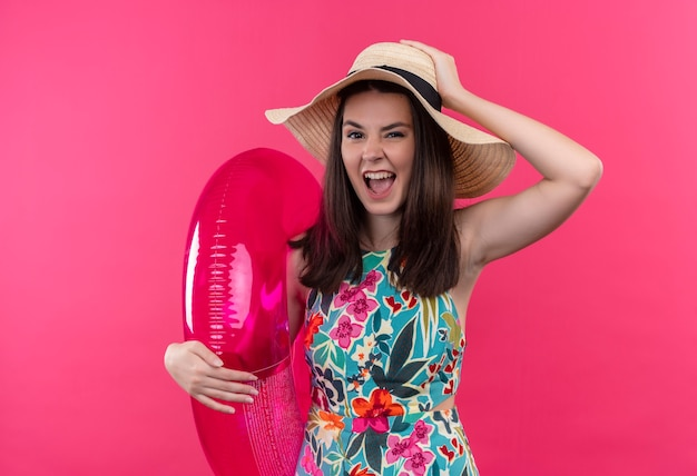 De zelfverzekerde jonge vrouw die hoed draagt die zwemt ring houdt en hand op hoofd op geïsoleerde roze muur zet