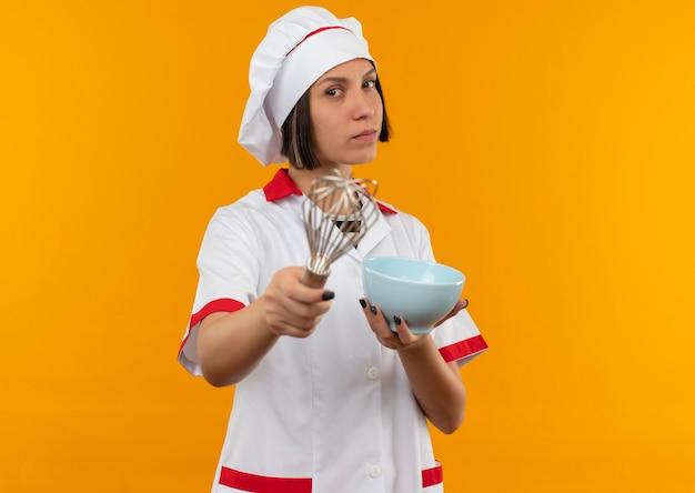 De zelfverzekerde jonge vrouwelijke kok in eenvormige chef-kok die zich uitstrekt zwaait en houdt kom op zoek geïsoleerd op oranje met exemplaarruimte