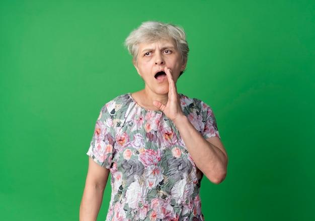 De zelfverzekerde oudere vrouw houdt de hand dicht bij de mond en doet alsof ze iemand belt die op de groene muur is geïsoleerd