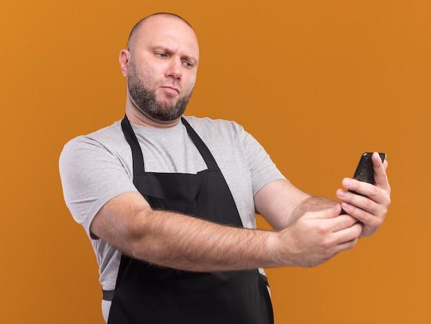 De zelfverzekerde slavische mannelijke kapper van middelbare leeftijd in uniform neemt een selfie geïsoleerd op een oranje muur