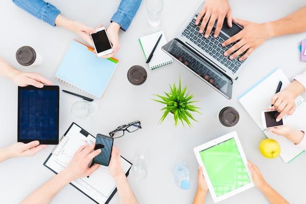 De zes mensen werken met apparaten op de desktop. uitzicht van boven