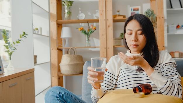 De zieke aziatische jonge pil van de vrouwenholding neemt thuis een kijkende geneeskundezitting op laag