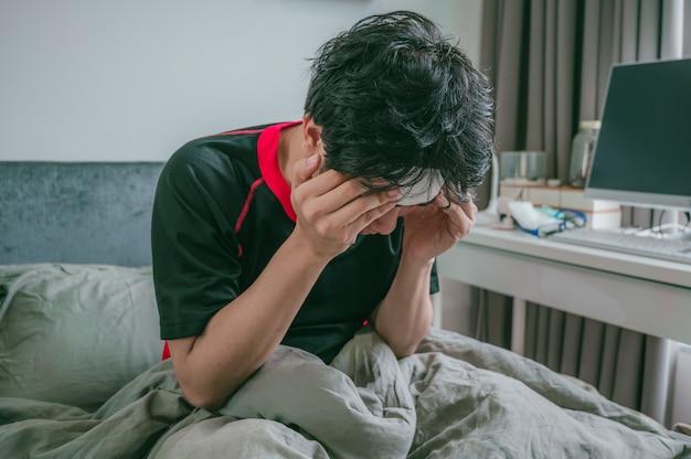 De zieke aziatische mens is hoofdpijn en gebruikt zijn handen om hoofd te houden