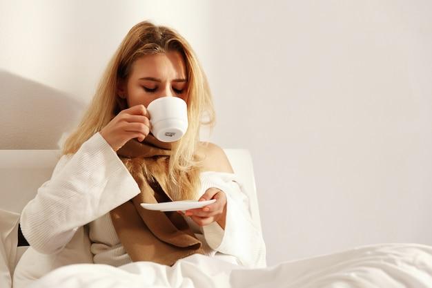 De zieke blonde vrouw ligt met een sjaal in het bed en drinkt hete thee