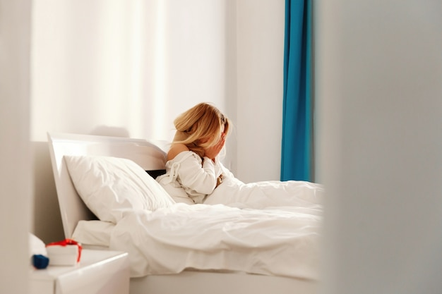De zieke blonde vrouw ligt met een sjaal in het bed en niest
