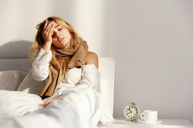 De zieke blonde vrouw ligt met een sjaal in het bed met hoofdpijn en koorts