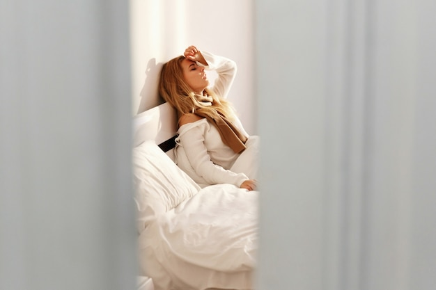 De zieke blonde vrouw ligt met een sjaal in het bed