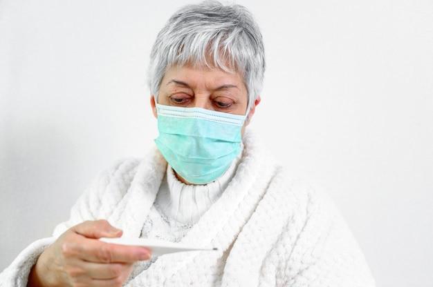 De zieke hogere thermometer van de vrouwenholding zit op bed.