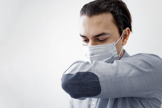 De zieke man hoest in zijn mouw of elleboog