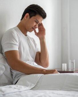 De zieke man zat op het bed en raakte haar hoofd aan met zijn hand.