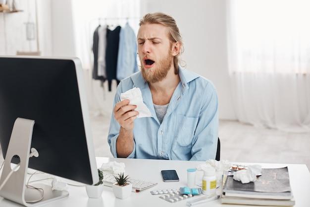 De zieke mannelijke beambte houdt zakdoek, niest, heeft ongelukkige en vermoeide uitdrukking, die tegen bureauachtergrond wordt geïsoleerd. ongezonde jongeman verspreidt bacteriën