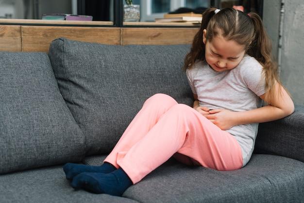 De zieke meisjeszitting op grijze bank lijdt aan maagpijn thuis