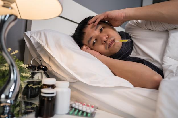 De zieke mens is hoofdpijn en gebruikt thermometer om zijn temperatuur in bed te controleren