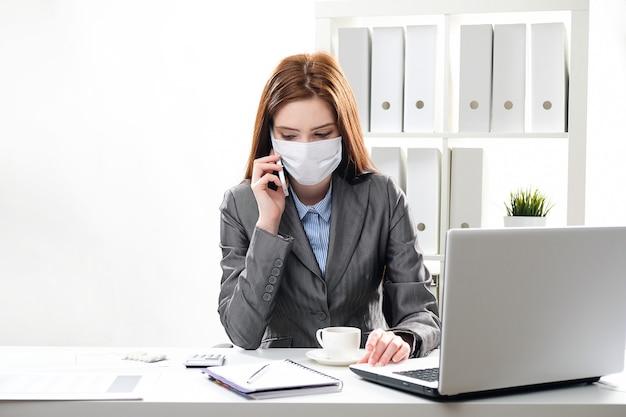 De zieke onderneemster in een beschermend medisch masker op kantoor gebruikt een mobiele telefoon