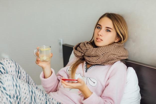 De zieke ongelukkige jonge vrouw ligt in een bed