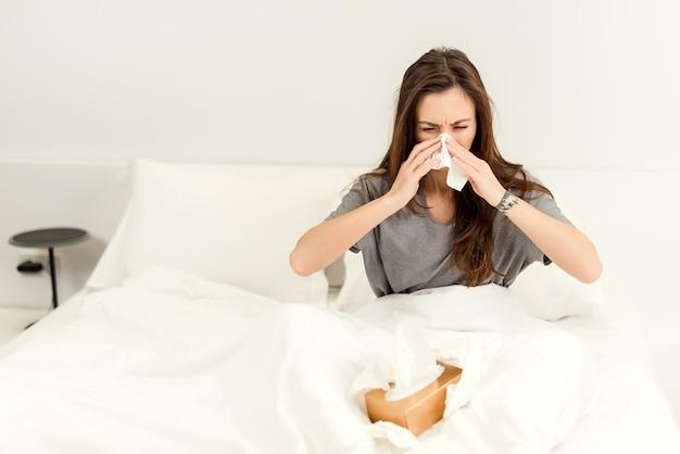 De zieke vrouw gebruikt servetten om haar neus schoon te maken en in bed in slaapkamer te niezen