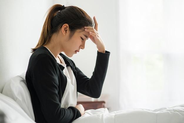 De zieke vrouw had hoofdpijn en de handen raakten haar hoofd op het bed.