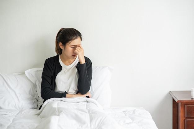 De zieke vrouw had hoofdpijn en legde haar hand op haar neus op het bed.