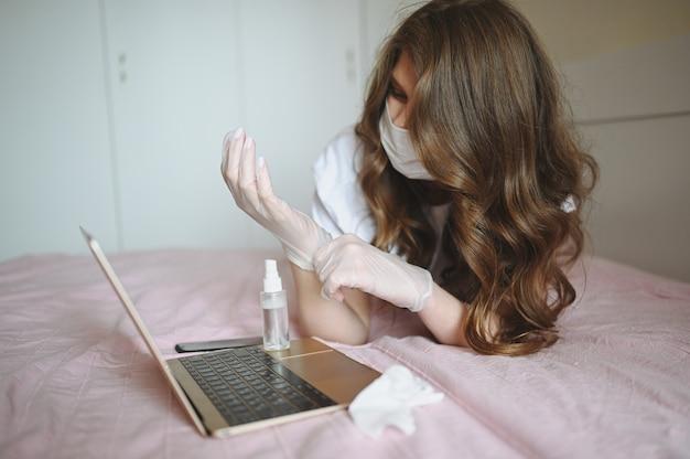 De zieke vrouw in gezichts beschermend masker met laptop en handalcoholdesinfecterend middel in bed zet op medische handschoenen