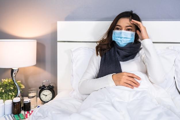 De zieke vrouw in medisch masker is hoofdpijn en lijdt aan virusziekte en koorts in bed, coronavirus pandemisch concept.