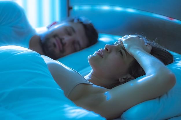 De zieke vrouw lag naast een man in bed. nachttijd