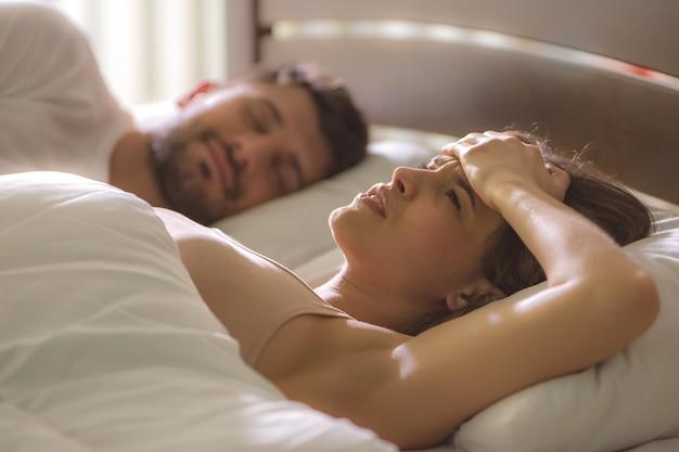 De zieke vrouw lag naast een man in bed