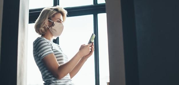 De zijaanzichtfoto van een vrouw met kort blond haar die een medisch masker op het gezicht draagt, gebruikt een telefoon bij het raam