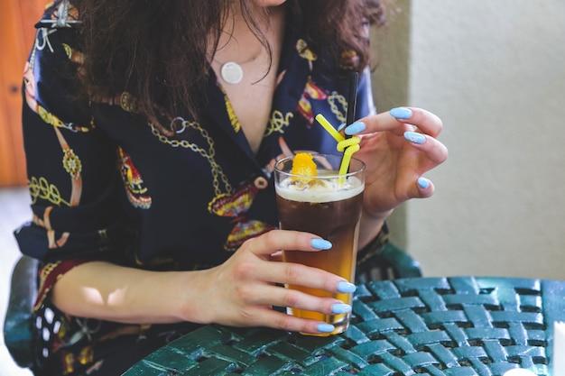 De zijaanzichtvrouw drinkt zachte limonade met een geel stro aan de lijst