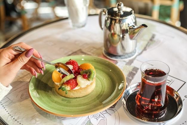 De zijaanzichtvrouw eet fruitdessert met een glas thee