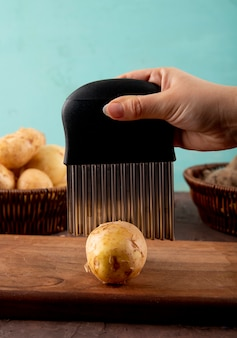 De zijaanzichtvrouw snijdt aardappels op een raad met bieten in een mand