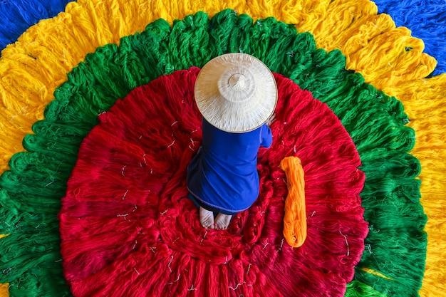 De zijdewever maakte een rol met kleurrijke zijden draden voordat hij ze tot stof weefde.