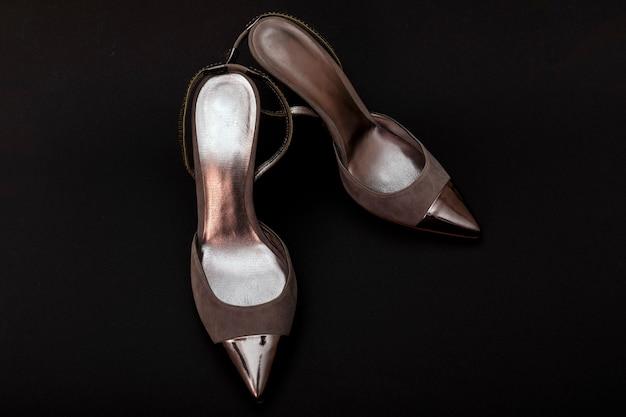 De zilveren geïsoleerde schoenen van de leervrouw