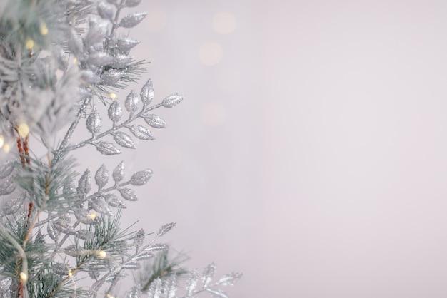 De zilveren glanzende bal die van het nieuwjaar op een spartak hangt. lichten en slingers op een grijze sneeuwachtergrond.
