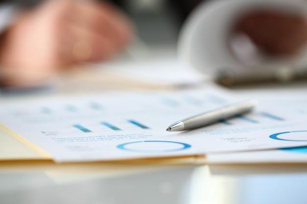 De zilveren pen ligt bij belangrijk document op lijst in bureauclose-up met zakenman op achtergrond. papierwerk baan handel balans bank krediet lening geld investeren betaling irs handel partnerschap concept