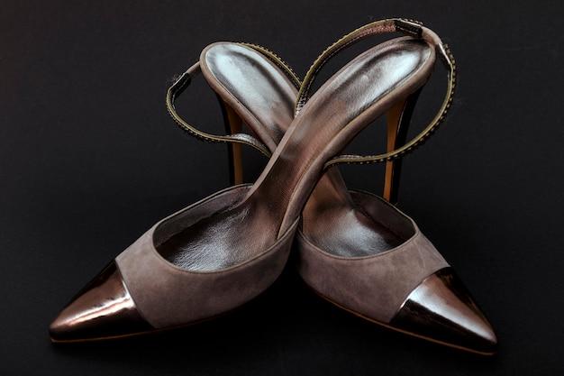 De zilveren schoenen van de leervrouw die op zwarte worden geïsoleerd