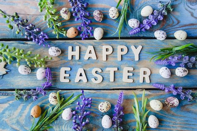 De zin happy easter in houten letters met paarse bloemen en distel eieren op een versleten blauwe houten tafel.