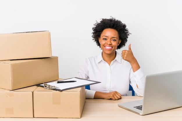 De zitting die van de pakhuismanager leveringen met laptop controleren die en duim glimlachen omhoog opheffen