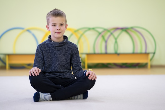 De zitting en de relaxiong van de jong kindjongen op de vloer binnen sportenruimte in een school na opleiding.