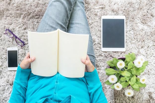 De zitting van de close-upvrouw voor las een boek ontspant binnen tijd