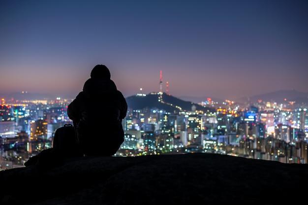 De zitting van de jonge mensenreiziger op de rots die de stad van seoel nacht bekijken