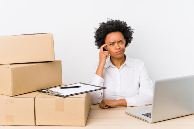De zitting van de pakhuismanager het controleren van leveringen met laptop die tempel met vinger richten, denkend, geconcentreerd op taak.