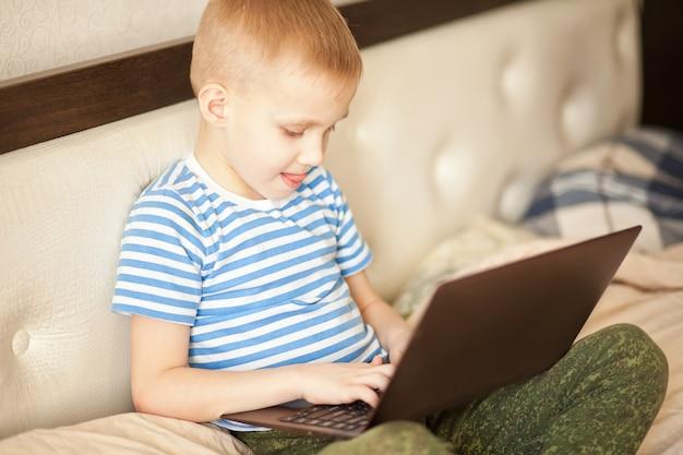 De zitting van het jongensjonge geitje op het bed en het gebruiken van een digitaal tabletlaptop notitieboekje.