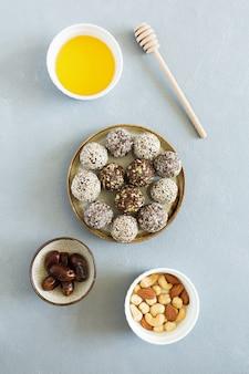 De zoete ballen van de suikergoedenergie met noten en gedroogd fruit op plaat leggen op grijze achtergrond