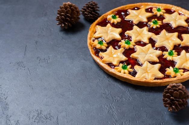 De zoete cake van het kerstmishuis met jam op donkere achtergrond