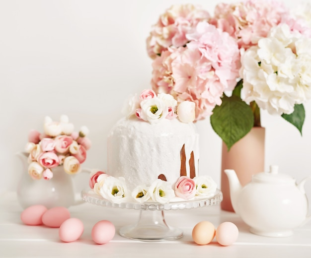 De zoete cake van pasen met bloemen en eieren