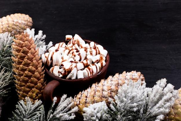De zoete heemst van het kerstmisvoedsel met chocolade in bruine kop op zwarte. plat leggen
