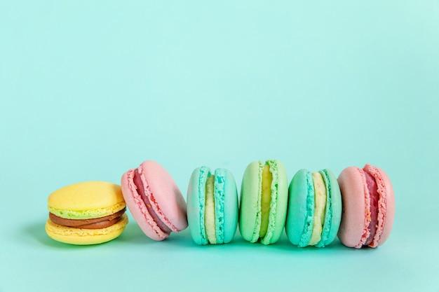 De zoete kleurrijke cake van het macarondessert die op blauw wordt geïsoleerd