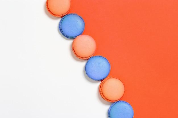 De zoete kleurrijke makarons in rij, heldere koekjes sluiten omhoog