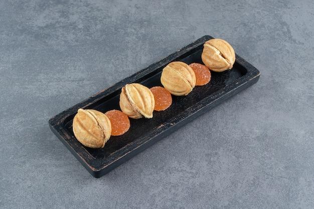 De zoete koekjesnoten van het gebak met het suikergoed van de fruitgelei