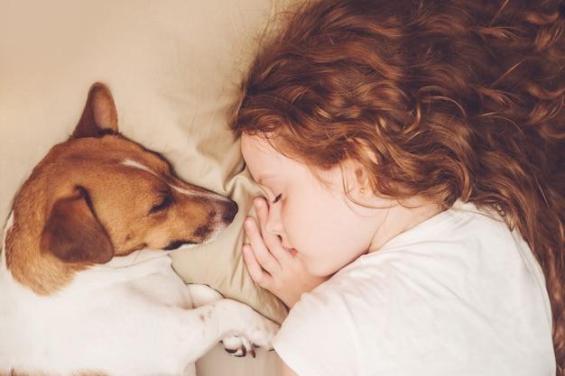 De zoete krullende meisje en de hond slapen in nacht.